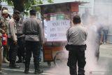 Petugas memadamkan api pada gerobak yang dibakar pedagang kaki lima (PKL) saat unjuk rasa di depan Gedung Pemkab, Kediri, Jawa Timur, Kamis (14/10/2021).  Unjuk rasa puluhan PKL tersebut guna menuntut pemerintah daerah setempat membuka kembali kawasan Simpang Lima Gumul (SLG) yang ditutup karena pemberlakuan pembatasan kegiatan masyarakat agar bisa kembali berjualan. Antara Jatim/Prasetia Fauzani/zk.