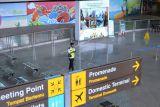 Petugas melintas saat hari pertama pembukaan kembali penerbangan internasional di area Terminal Internasional Bandara Internasional I Gusti Ngurah Rai, Badung, Bali, Kamis (14/10/2021). Bandara Ngurah Rai resmi dibuka kembali untuk melayani penerbangan internasional namun hingga Kamis siang masih belum ada pengajuan 'slot time' penerbangan internasional dari maskapai penerbangan di bandara tersebut. ANTARA FOTO/Fikri Yusuf/nym.