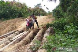 Bhabinkamtibmas di Aceh Utara bantu petani seberangi jembatan darurat