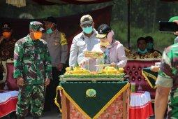 Foto - Anggota DPR Idah Syahidah potong tumpeng dimulainya pembangunan Kodim di Boalemo