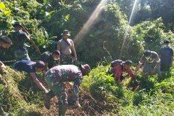Warga dan anggota TMMD bergotong royong bersihkan Parit