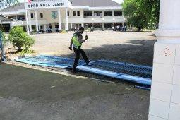 Anggota polisi melintasi pintu pagar DPRD Kota Jambi yang roboh