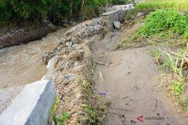 Tanggul penahan banjir jebol  akibat luapan air Sungai Batang Ayumi