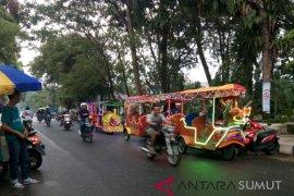 Anak-anak antre naik kendaraan hias