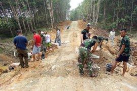 TNI bersama warga  gotong royong membuat drainase