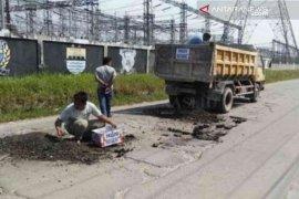 Warga Bekasi memerbaiki kerusakan jalan secara swadaya