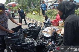 Mahasiswa dan polisi memungut sampah selesai aksi demo