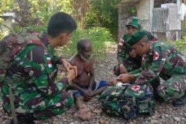 Prajurit TNI menolong warga Mimika, Papua, yang dilaporkan sakit