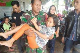 Anggota TNI evakuasi korban banjir di Kibin, yang terserempet motor