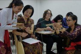 Menulis aksara Bali di daun lontar