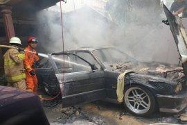 Mobil sedan terbakar akibat arus pendek