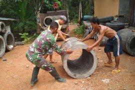 Warga dan anggota satgas TMMD dorong material gorong-gorong