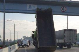 Baru pertama terjadi, bak truk tersangkut ke jembatan penyeberangan orang