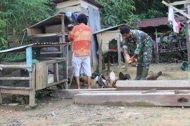 Personel TMMD ini, bantu Bu Ratna ngasi makan ayam