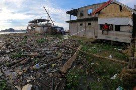 Sampah rumah tangga dan potongan kayu di Sungai Batanghari