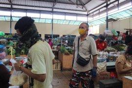 Seorang petugas pasar tengah mengingatkan masyarakat menggunakan masker Page 5 Small