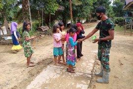 Anggota TMMD berbagi kecerian bersama anak-anak desa