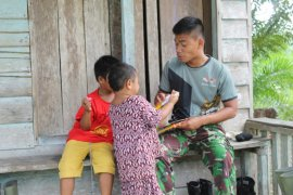 Jalin komunikasi anggota TMMD bermain bersama bocah