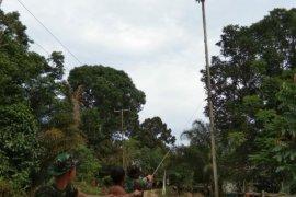 Anggota Satgas TMMD 108 bantu warga tebang pohon pinang