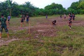 Satgas TMMD bermain sepak bolabersama pemuda