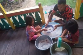 Anggota TMMD bantu warga buatkue dari tepung beras