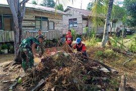 TMMD 108 bantu warga bersihkan sampah didepan rumah