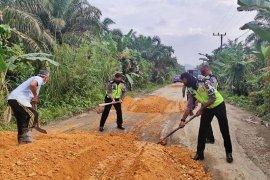 Polisi  tambal jalan berlubang saat operasi patuh di Aceh Timur