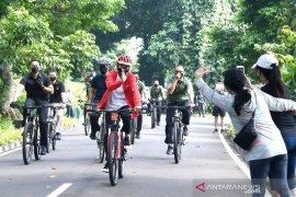 Presiden Jokowi ditemani Kaesang bersepeda dan bagikan masker di Kebun Raya Bogor