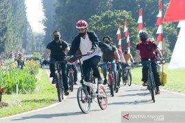 Presiden ditemani Kaesang bersepeda dan bagi-bagi masker