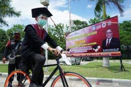 """Wisuda """"drive thru"""" UNG, Yandri Mahmud pakai sepeda"""