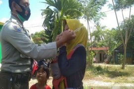 Bhabinkamtibmas bagikan masker ke warga