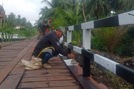 Warga dan TNI mulai mengecat pagar Jembatan Handil Samsu