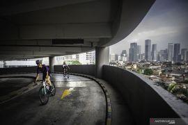 Warga bersepeda di jalan melingkar gedung parkir