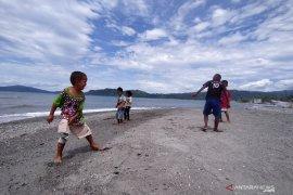 Anak-anak korban tsunami bermain di pantai