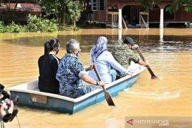 Raja Malaysia tinjau lokasi banjir dengan sampan