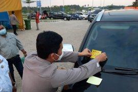 Petugas pasang stiker kepada pengendara yang berkas prokesnya lengkap