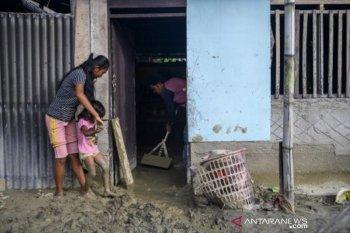Warga bersihkan rumahnya dari lumpur akibat banjir