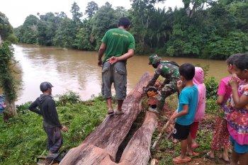 Praka Firmansyah potong pohon tumbang mengunakan chainsaw