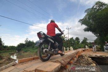 Warga melintas di jembatan darurat