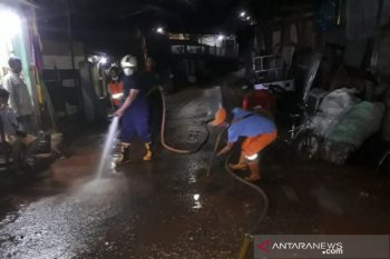 Petugas bersihkan lumpur luapan kali di Pasar Rebo