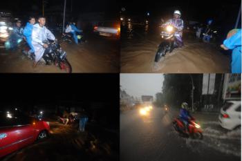 Pengendara menerobos banjir di jalan utama Kota Manado