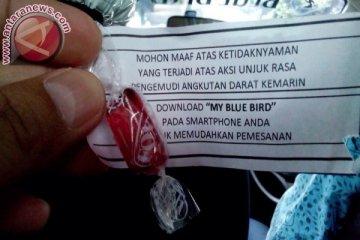 Tidak hanya gratis, pengemudi Blue Bird bagi permen dan selebaran