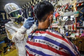 Tukang cukur pakai APD COVID-19