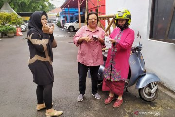 Seorang ibu berkendara Vespa berbagi masker peringati Hari Kartini