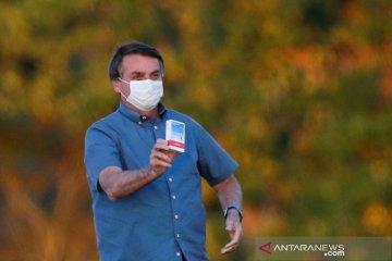 Presiden Brazil Jair Bolsonaro berbincang dengan menkes positif corona tanpa menggunakan masker