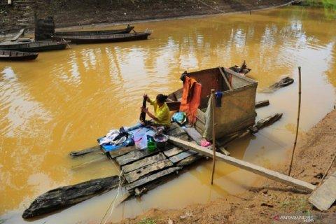 Warga mencuci pakaian di sungai yang keruh