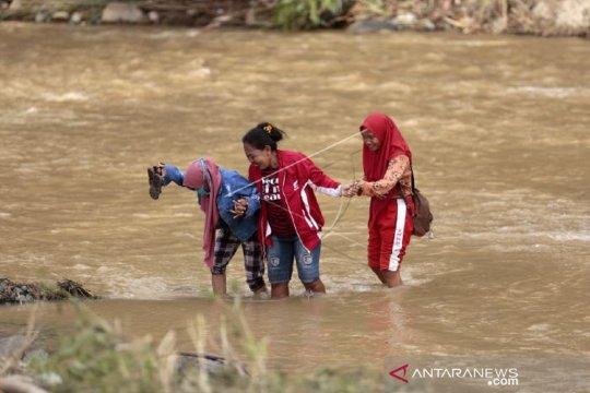 Foto - Warga Bone Bolango lintasi sungai deras setelah jembatan hanyut