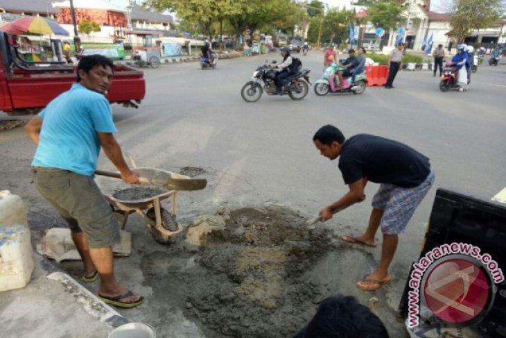 Warga Gotong Royong Menambal Jalan Negara