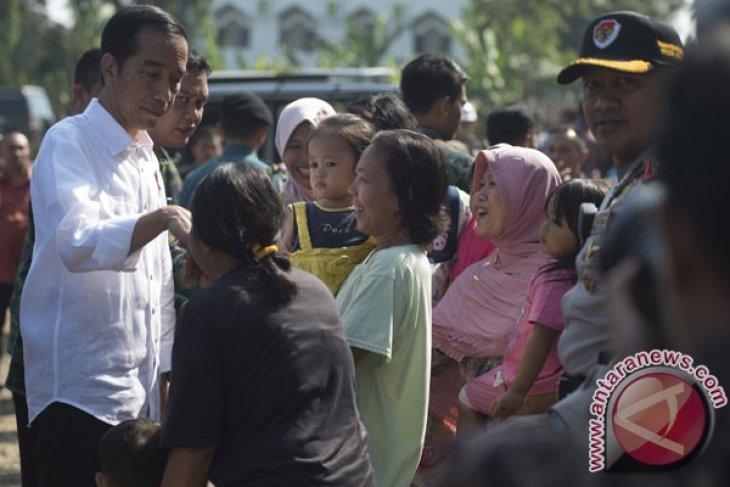 President Jokowi helps distribute food packages