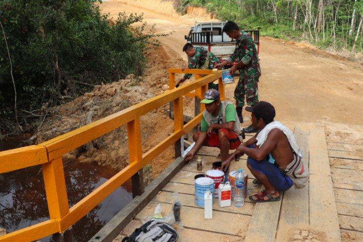 Prajurit Satgas TMMD dan warga percepat pengecatan jembatan